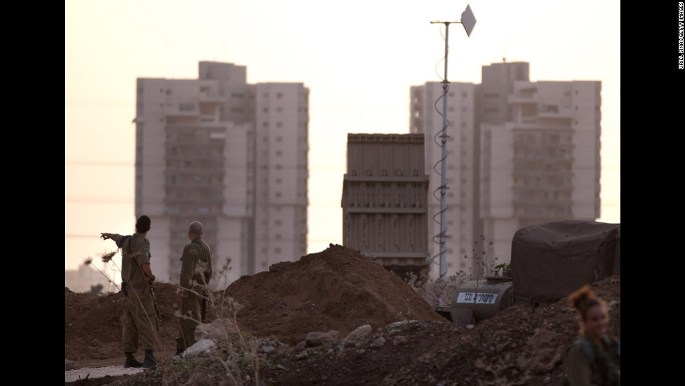 Israeli soldiers stand guard by the Iron Dome defense system launch site on Saturday, November 17, in Tel Aviv, Israel.
