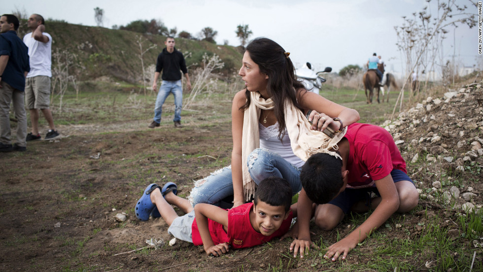 An Israeli woman and her children take cover as sirens wail in Tel Aviv on Saturday, November 17.