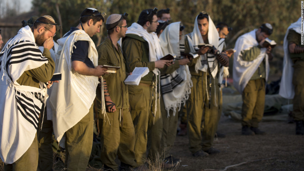 Israeli soldiers wearing prayer shawls conduct morning prayers Sunday, November 18, at an Israeli army deployment area.