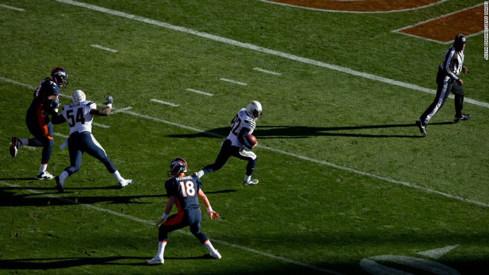 Safety Eric Weddle of the Chargers runs back an interception for a touchdown past quarterback Peyton Manning of the Broncos during the first quarter on Sunday.