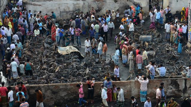 Onlookers gather around the wreckage of fire-damaged rickshaws in a slum in Dhaka, Bangladesh, on Sunday.