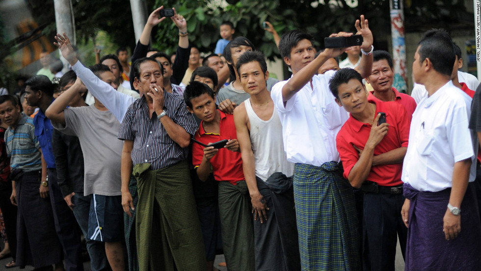 Local residents line up along the street with cameras as Obama's motorcade drives to the Parliament House in Yangon.
