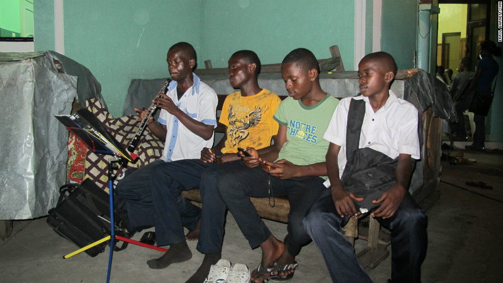 The Kinshasa orchestra does not have enough instruments so these boys must take 20-minute turns while practicing.