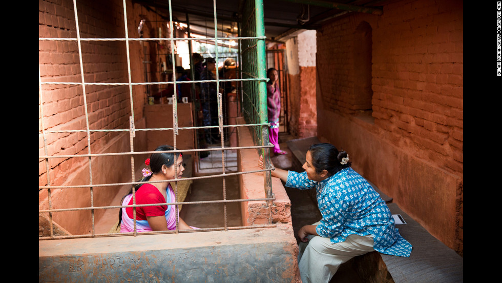 "Basnet talks to an inmate in Kathmandu. ""Meeting and spending time with the children and the mothers in jail, you realize that Pushpa is their only hope,"" said photographer Palani Mohan."