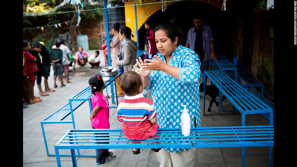Basnet applies moisturizer cream to one of the children in Kathmandu.