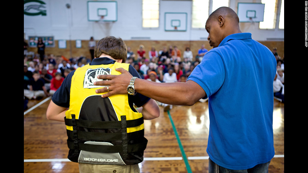 "Children at the Gesu School learn how to put on a life jacket. ""As a child, I never went around water,"" Butts said. ""I never went swimming. I didn't know anything about water or life jackets and water safety."""