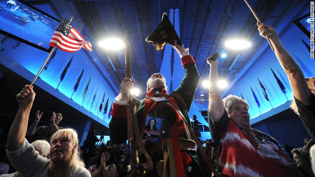 William Temple (C), in colonial dress, and other Tea Party supporters cheer at the Tea Party Unity Rally at The River at Tampa Bay Church ahead of the Republican National Convention, in Tampa, Florida, on August 26, 2012.  AFP PHOTO / ROBYN BECK        (Photo credit should read ROBYN BECK/AFP/GettyImages)