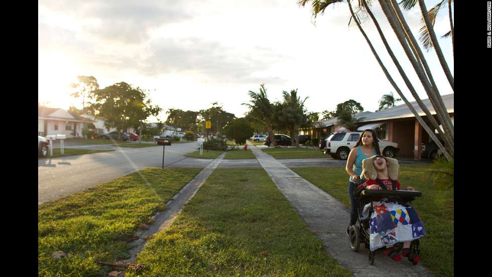 "Mandy ""Mimi"" Alvarado walks her brother Isaac Santiago around their neighborhood in Greenacres, Florida. Isaac uses a wheelchair, but his older sister takes him to the park next to their home and around their neighborhood."