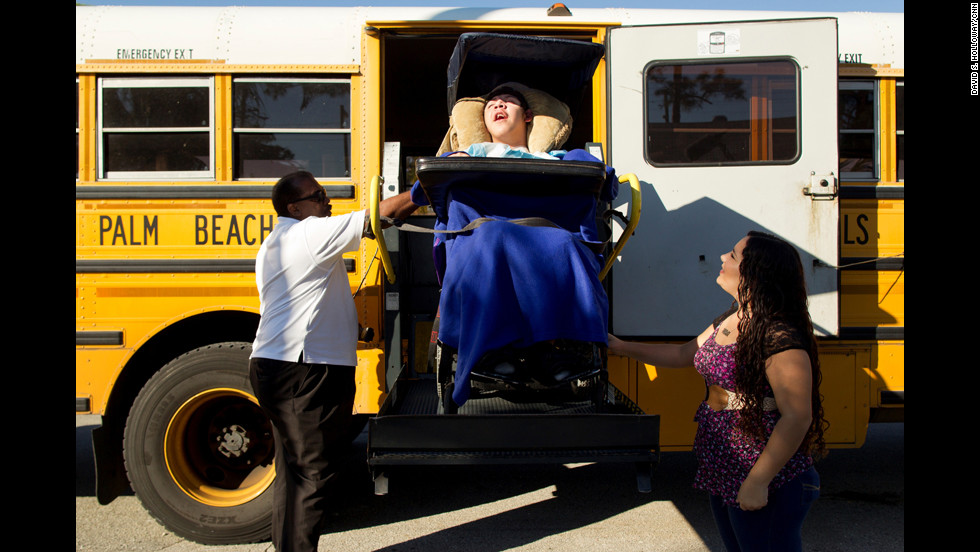 Mimi waits to greet Isaac as he is lowered down from the bus he rides to school.