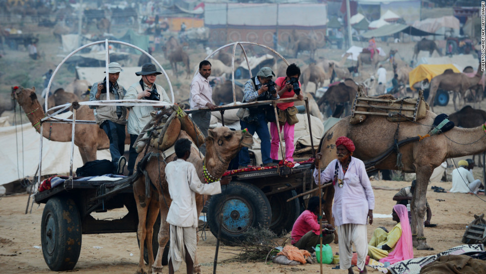 Asian tourists take photographs of camel traders as they get a ride on a camel cart through the fairgrounds on Wednesday.