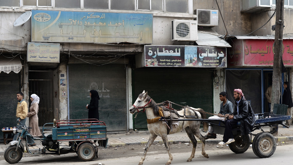 Syrians ride on a horse-drawn cart in the streets of the Tarik al-Bab neighborhood in Aleppo on Sunday, November 18.