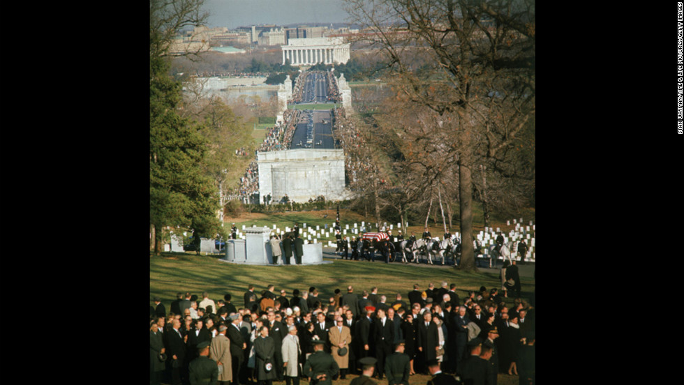 A horse-drawn caisson bears the body of President John F. Kennedy into Arlington National Cemetery.