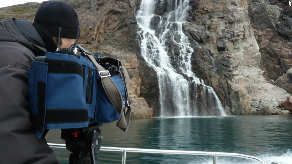CNN camera woman Claudia Otto films a waterfall. There is enough water for farming in Greenland, using it for irrigation remains a problem.