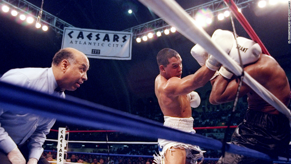 Camacho pins Sugar Ray Leonard to the ropes as referee Joe Cotez looks on during a bout in Atlantic City on March 1, 1997. Camacho won with a knockout in the fifth round, ending Leonard's comeback effort.