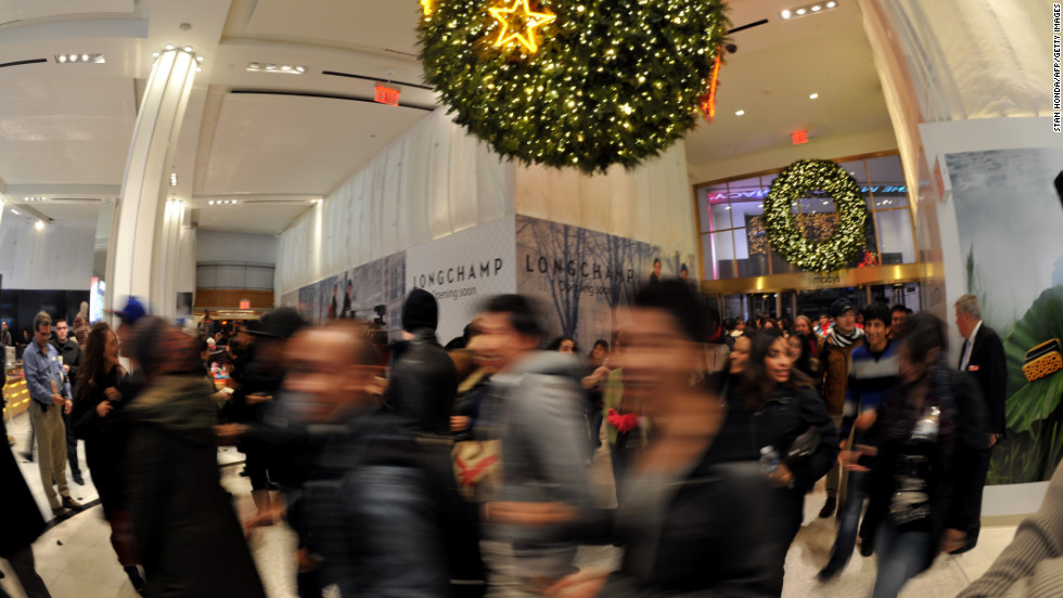 Shoppers rush into Macy's in New York at midnight.