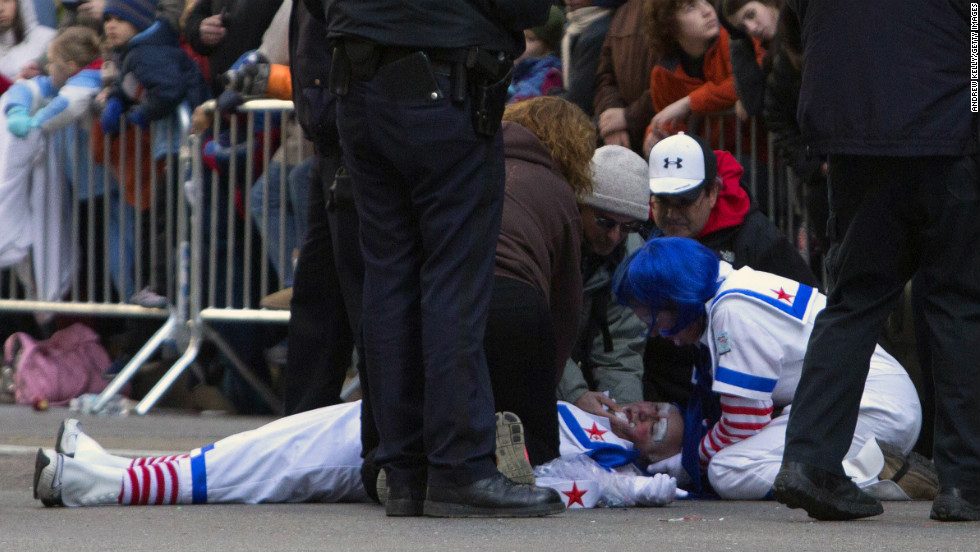An emergency rescue crew attends to a man dressed as a clown who collapsed during the parade.