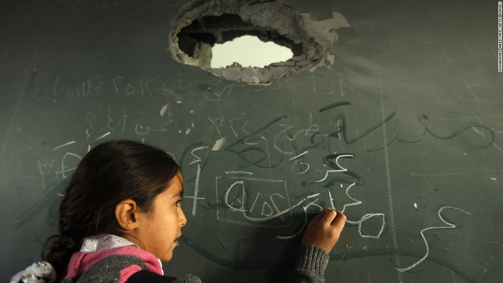 A Palestinian schoolgirl writes on the blackboard of a classroom in Gaza City on Saturday.