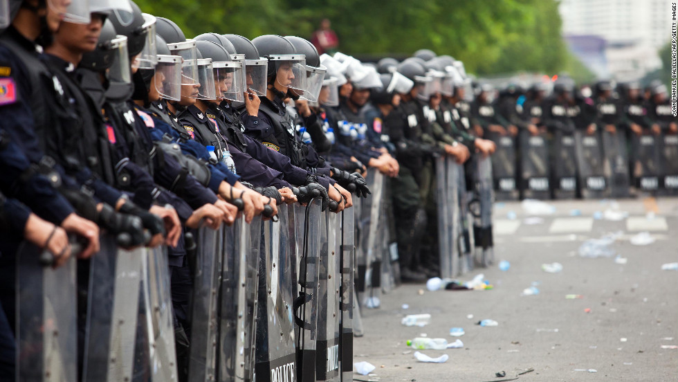 Thai riot police officers stand guard during an anti-government protest in Bangkok on Saturday.  Thai police fired tear gas and detained dozens of people as tensions flared.