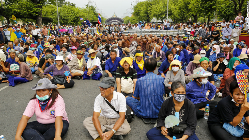 Protesters and Buddhist monks sit on the ground in front of riot police during a protest on Saturday.