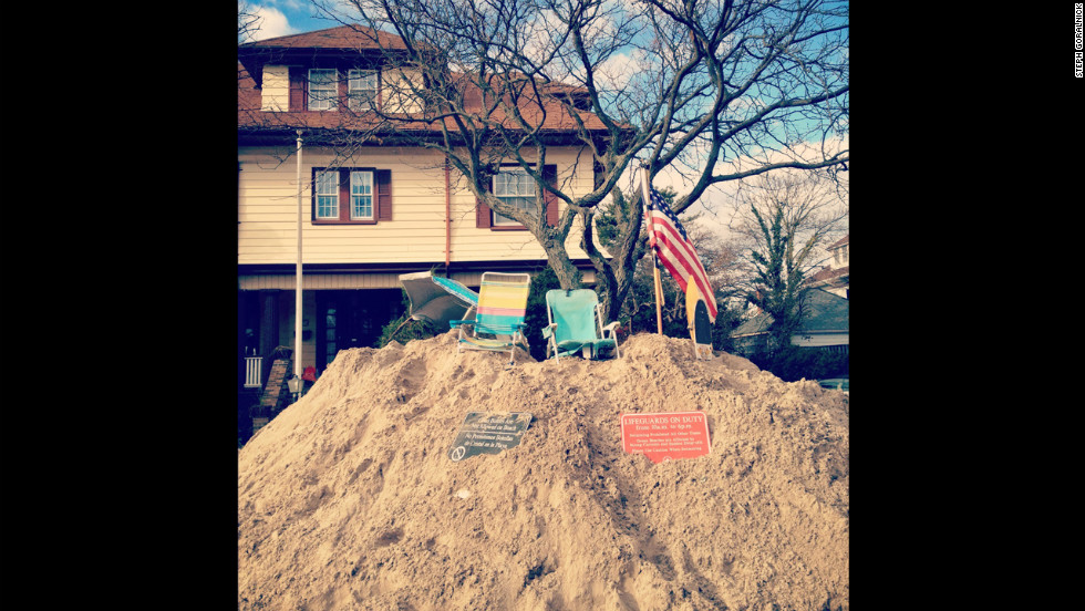 Residents show the storm hasn't taken their sense of humor by making the most of the sand on the streets that washed ashore from the beach blocks away.