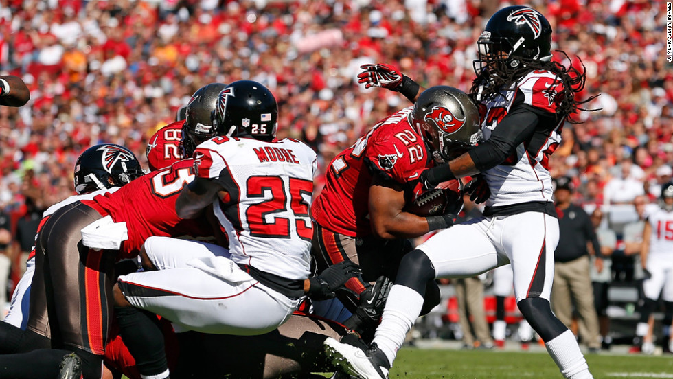 Running back Doug Martin of the Buccaneers is tackled by defender Dunta Robinson of the Falcons on Sunday.