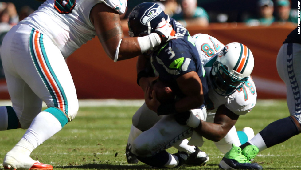 Quarterback Russell Wilson of the Seahawks is sacked by Tony McDaniel of the Dolphins on Sunday.