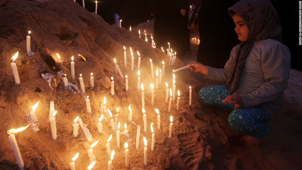 A girl lights a candle next to the Imam Hussein shrine as part of the ritual ceremony of Ashura in Karbala, Iraq, on November 25, 2012.