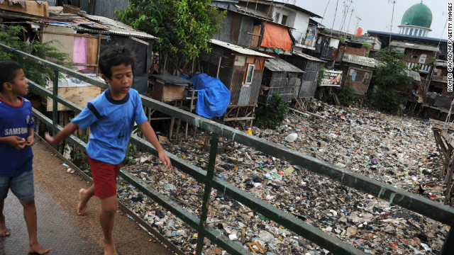 (File photo) Children walk on a footbridge over the polluted Cipinang river in Jakarta on November 13, 2012