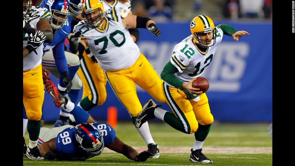 Quarterback Aaron Rodgers of the Green Bay Packers gets tripped up by No. 99 Chris Canty of the New York Giants on Sunday.