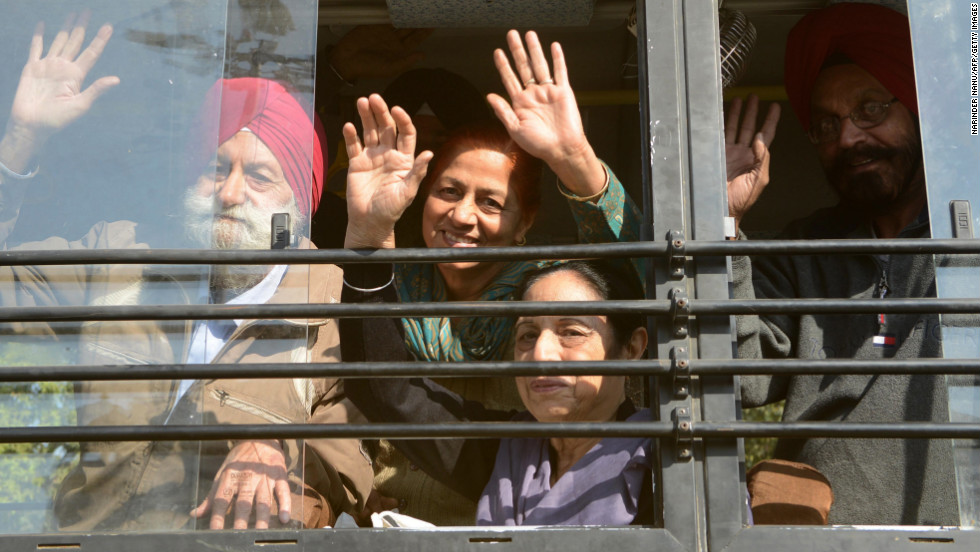 Indian Sikh pilgrims wave from a bus at the railway station in Amritsar on Sunday, November 25. Thousands of Sikh pilgrims were expected to travel to Pakistan to celebrate Guru Nanak Dev's birthday.