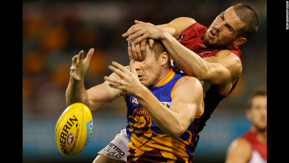 Ryan Harwood of the Brisbane Lions and James Magner of the Melbourne Demons compete for a mark during an Australian Football League match on July 1 in Brisbane, Australia.