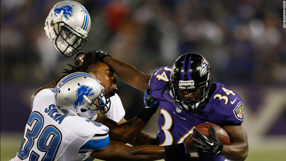 Jonte Green of the Detroit Lions loses his helmet while being stiff-armed by Bobby Rainey of the Baltimore Ravens as Ricardo Silva tackles him on August 17 in Baltimore, Maryland.