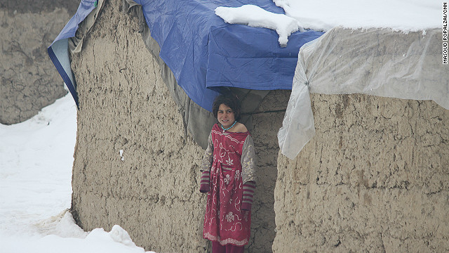 A child refugee shivers in the cold weather in a makeshift home in the eastern part of Kabul, Afghanistan.