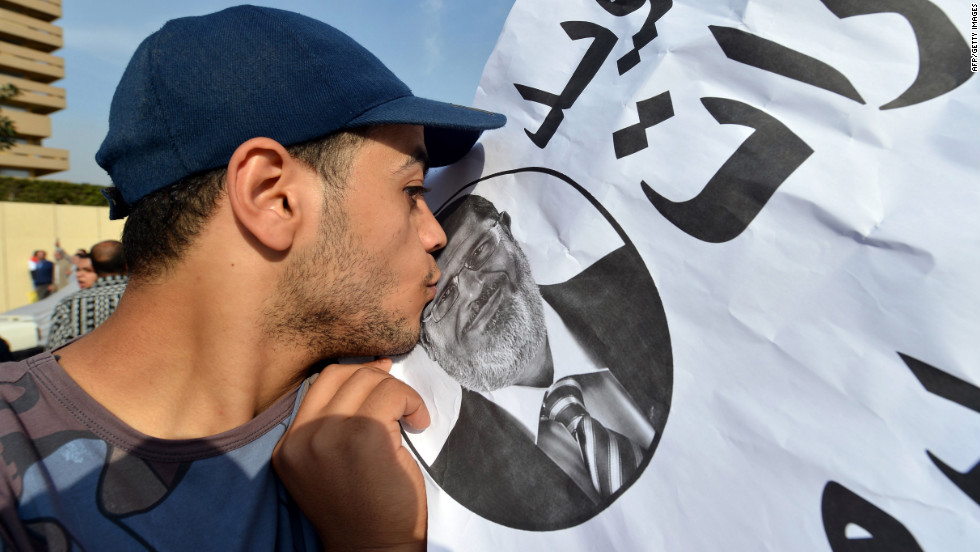 A man kisses a portrait of Morsy during a gathering of thousands of Islamists in front of Cairo University on Saturday, December 1.