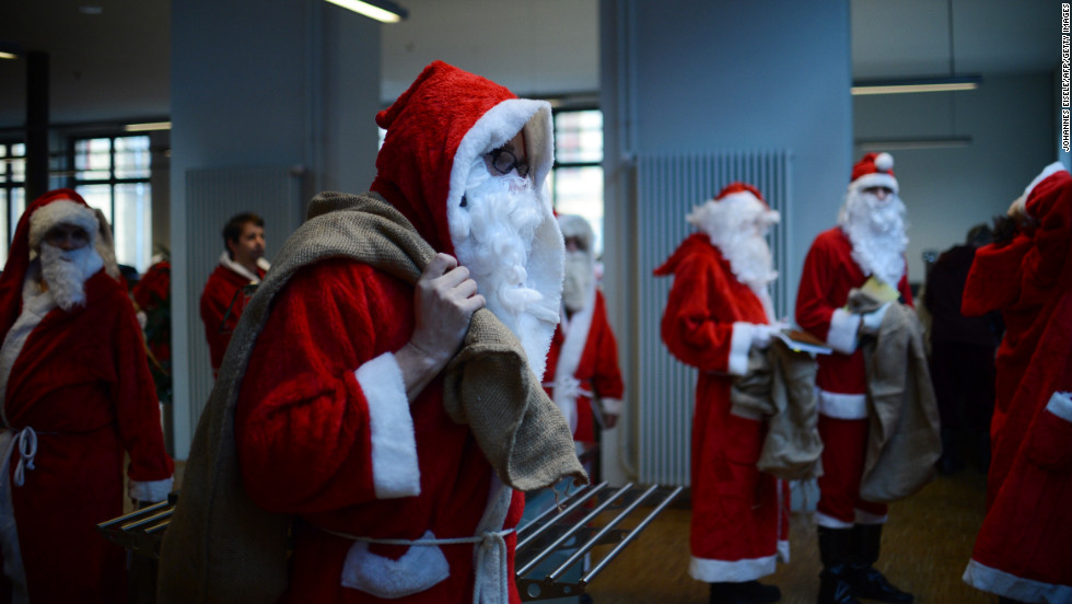 Men dressed as Santa Claus carry sacks through the meeting of volunteer Santa Clauses and angels on December 1 in Berlin.