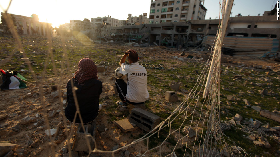 Bilal Abu Samaan (right) and Ala Ayoub sit in the rubble of the bombed stadium.
