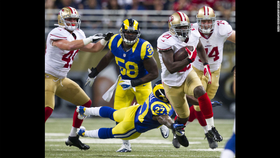 Running back Frank Gore of the San Francisco 49ers evades Quintin Mikell of the St. Louis Rams on Sunday.