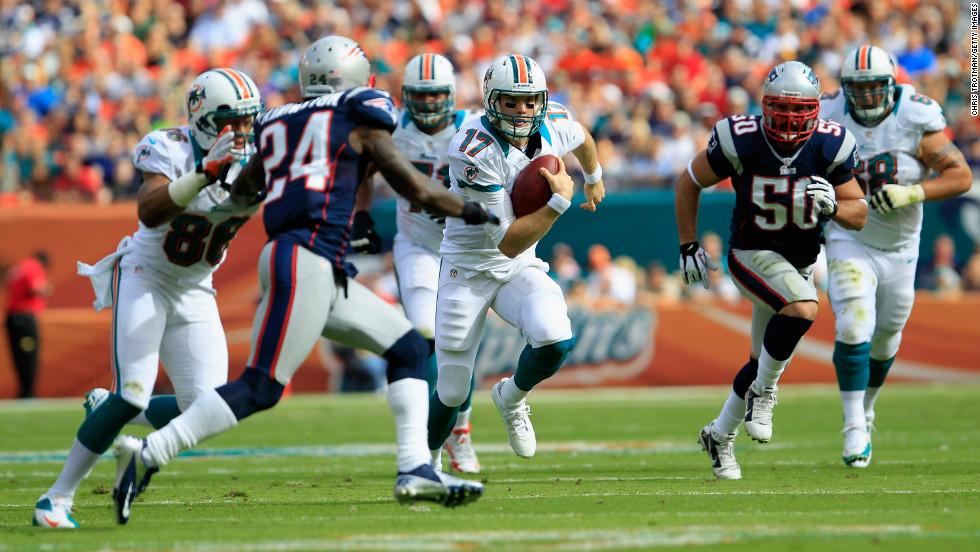 Quarterback Ryan Tannehill of the Miami Dolphins runs the ball against cornerback Kyle Arrington of the New England Patriots on Sunday.