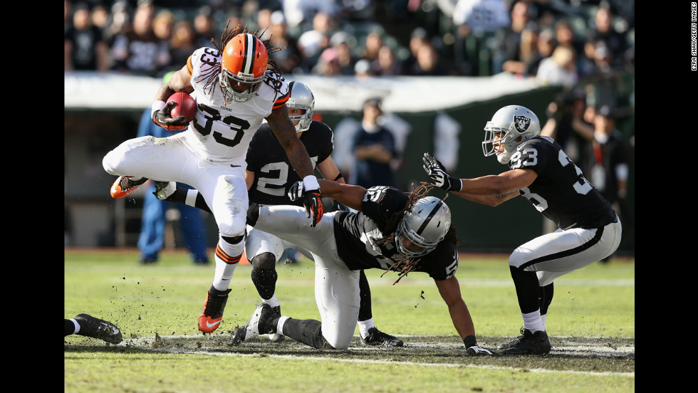 Trent Richardson of the Cleveland Browns jumps over Philip Wheeler of the Oakland Raiders on Sunday.