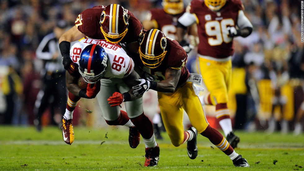 Martellus Bennett of the Giants catches a 22-yard pass as he is tackled by Giants defenders on Monday.
