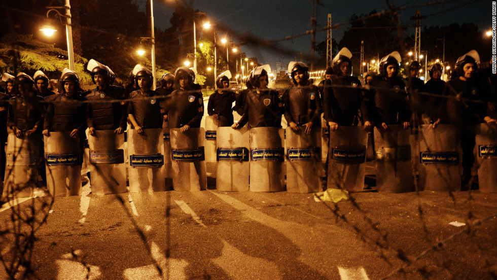 Egyptian riot police stand behind barbwire as thousands of Egyptian demonstrators march to the presidential palace in Cairo, Egypt, on Tuesday, December 4.