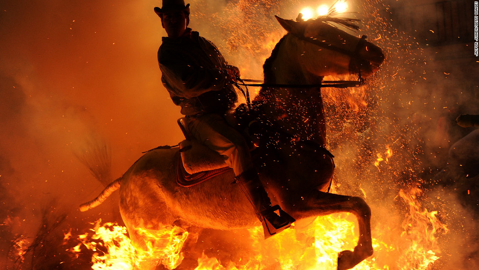 <strong>January 16:</strong> A man rides a horse through a bonfire in the small village of San Bartolome de Pinares, Spain, in honor of San Anton, the patron saint of animals.
