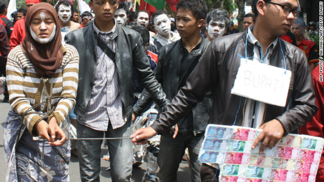 Demonstrators dramatize Aceng Fikri towing his second spouse Fany Octora in West Java province on December 6, 2012.