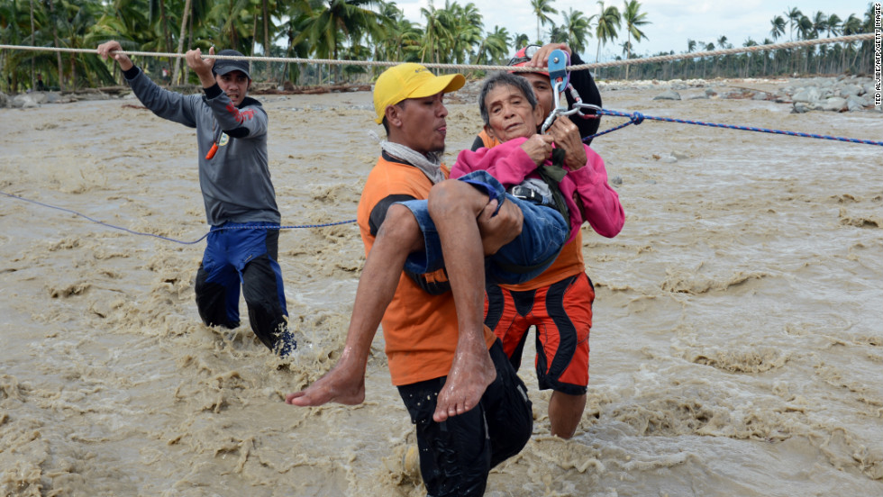 A rescue worker carries an elderly resident across a surging river in New Bataan on December 6.