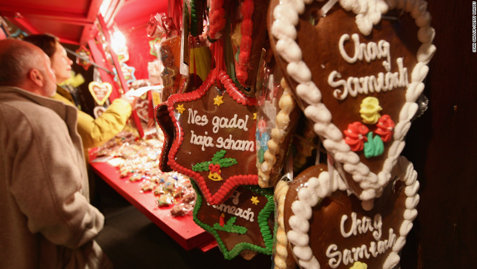 Jewish bakers are busy with more than just doughnuts and latkes during this time of year. Here, traditional gingerbread hearts and Stars of David with Hebrew inscriptions in Latin letters on them hang at a stall at the annual Hanukkah market at the Berlin Jewish Museum.