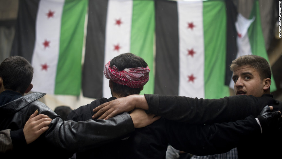 Rebel fighters take part in a demonstration against the Syrian regime after Friday prayers in Aleppo on December 7.