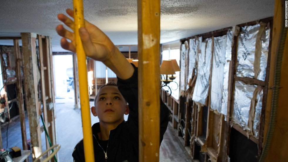 Ryan Panetta helps to repair his family's home in the Broad Channel section of Queens.