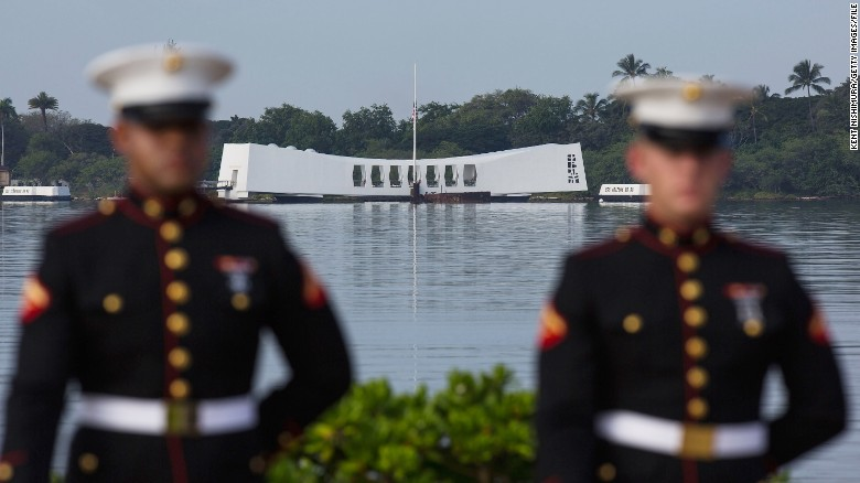 U.S. Marines stand at attention during a December 7, 2012, ceremony to commemorate Japan's attack on Pearl Harbor, Hawaii. The USS Arizona Memorial is in the background. The site was temporarily closed to visitors on May 27, 2015 for nine days after an accident damaged a dock and ramp leading to the memorial.