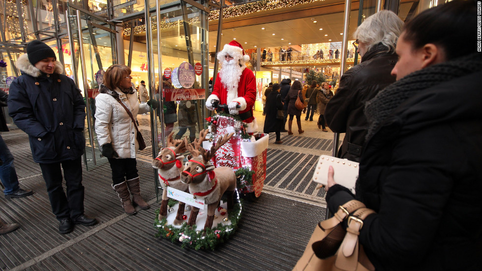 A customer holds the door of a shopping mall for a man dressed as Santa Claus on December 8, in Berlin.