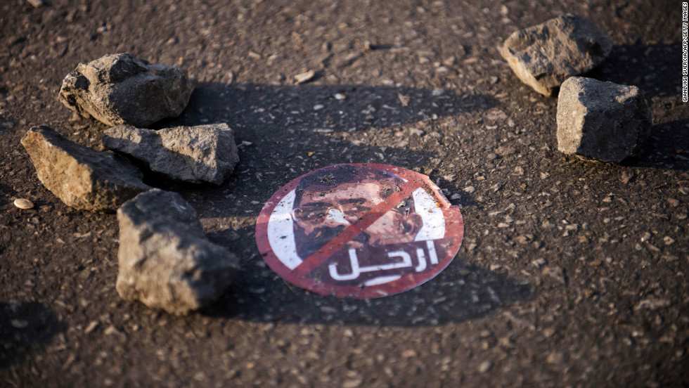 "A sticker depicting Egyptian President Mohamed Morsy reads ""leave"" on the ground near the presidential palace on December 8."